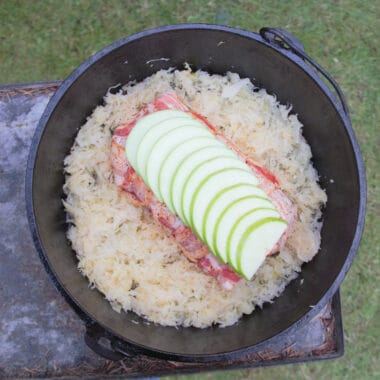 Looking directly down on a Dutch oven showing sauerkraut surrounding the bacon wrapped pork loin topped with fanned out apple slices before being cooked.
