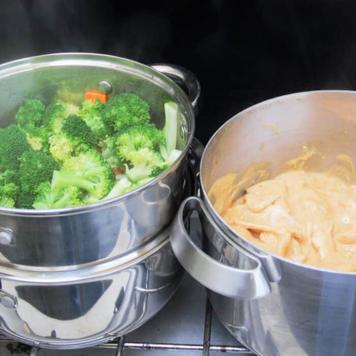 A camp gas stove with a steamer filled with vegetables and pot with chicken peanut sauce.