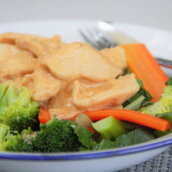 Looking across a camp plate serving of peanut chicken on top of steamed vegetables.