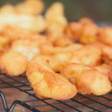 A cooling rack is topped with golden brown apple fritters shaped like chips.