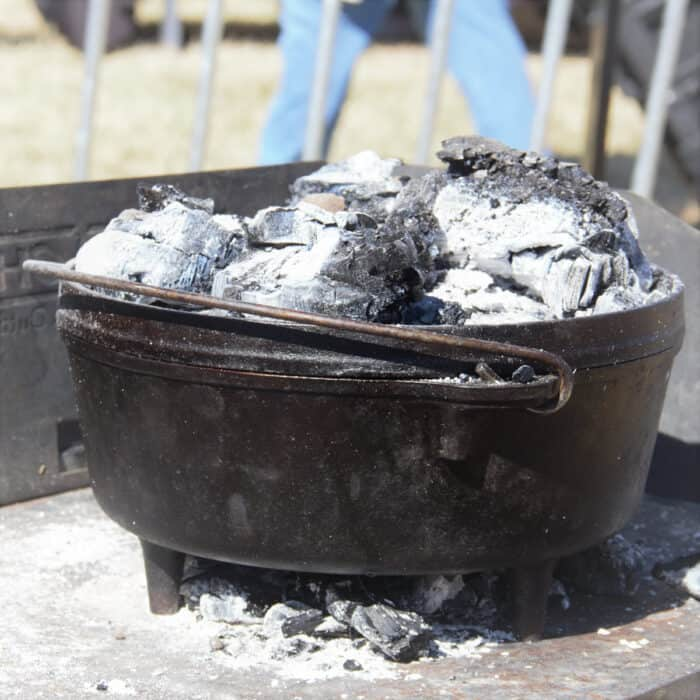 A Dutch oven with campfire coals above and below it cooking a dump cake.