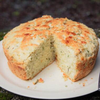 A round loaf of herb and garlic quick bread on a plate with a wedge cut out of it.