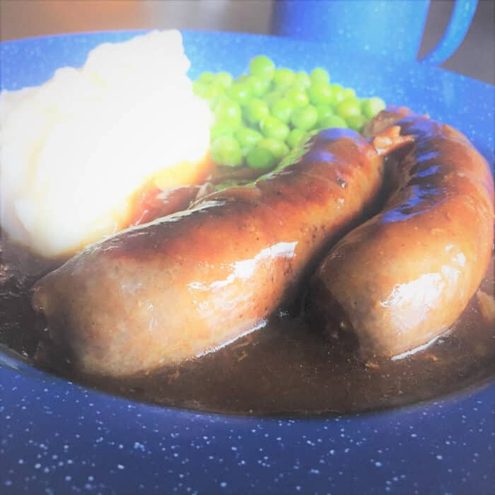 Close up of sausages with gravy on a blue camp plate with mashed potato and peas in the back ground.