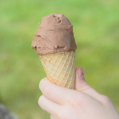 hand holding an ice cream cone filled with chocolate ice cream