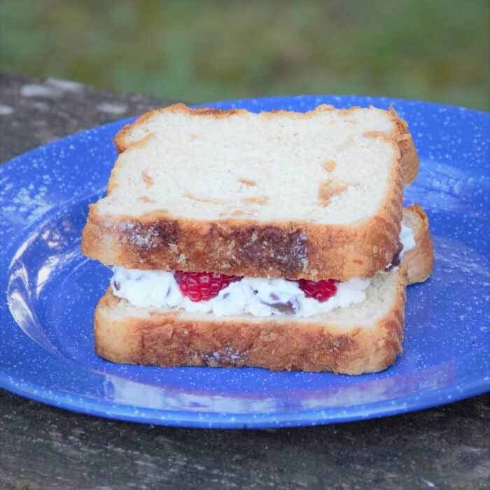 A ricotta chocolate and raspberry sandwich on a blue camp plate ready to be added to the pie iron to cook.