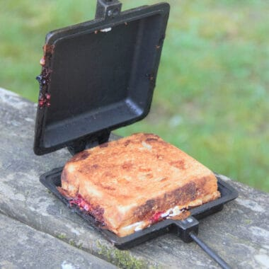 A open pie iron on a picnic table showing the chocolate raspberry ricotta toastie inside.