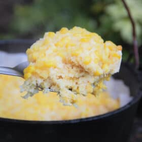 A spoon serving being shown with the creamy corn base, cornbread middle and kernel top with the full corn dump cake in the background.