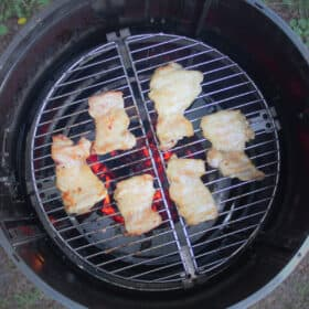 Looking down on 6 chicken thighs on a round grill over glowing red charcoals.