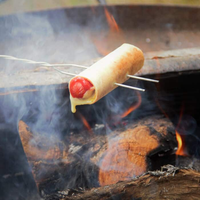 A hot dog wrapped in a tortilla with cheese oozing out being cooked over a campfire with a toasting fork
