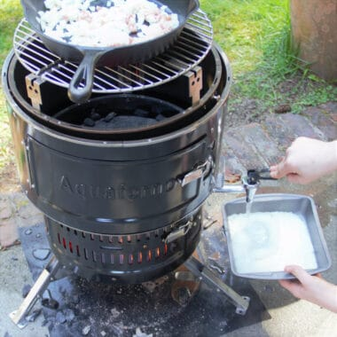 The Aquaforno barbecue with bacon and onion cooking in a skillet on the top while water from the bottom is being added to a tray of dehydrated mashed potato.