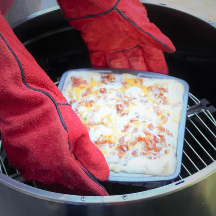 A square baking pan of loaded mashed potatoes being removed from the Aquoforno which was being used as a camp oven.
