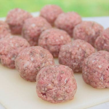 Chopping board covered in an even layer of round meatballs ready to be wrapped.