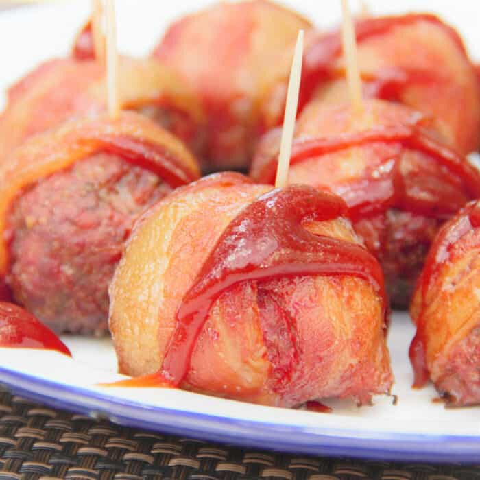 Close up of a Cheese Stuffed Bacon Wrapped Meatball on a serving plate with a toothpick in it, drizzle of sauce and other meatballs in the background.