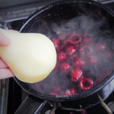 A black camp pot simmering with red wine and raspberries, with a peeled pear half being added.