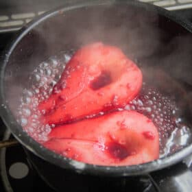 A black camp pot with two pear halves poaching in a red wine based liquid.