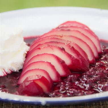 A white camp plate with a sliced pear sitting in a bed of red wine and raspberry sauce and a side of whipped cream.