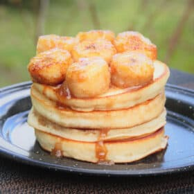 A black camp plate stacked with four pancakes and topped with suate honey banans with the syrup running down the side of the pancakes.