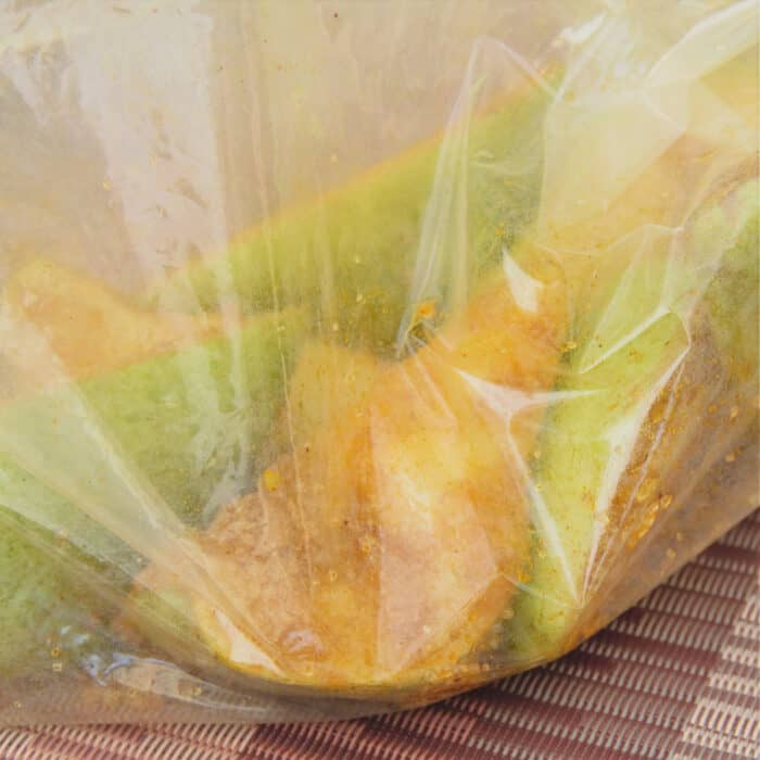 A plastic bag filled with pear quarters, the sugar, and seasonings.