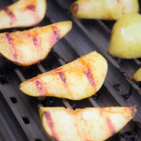 Grillgrates topped with well cooked pear quarters showing clear grill marks.