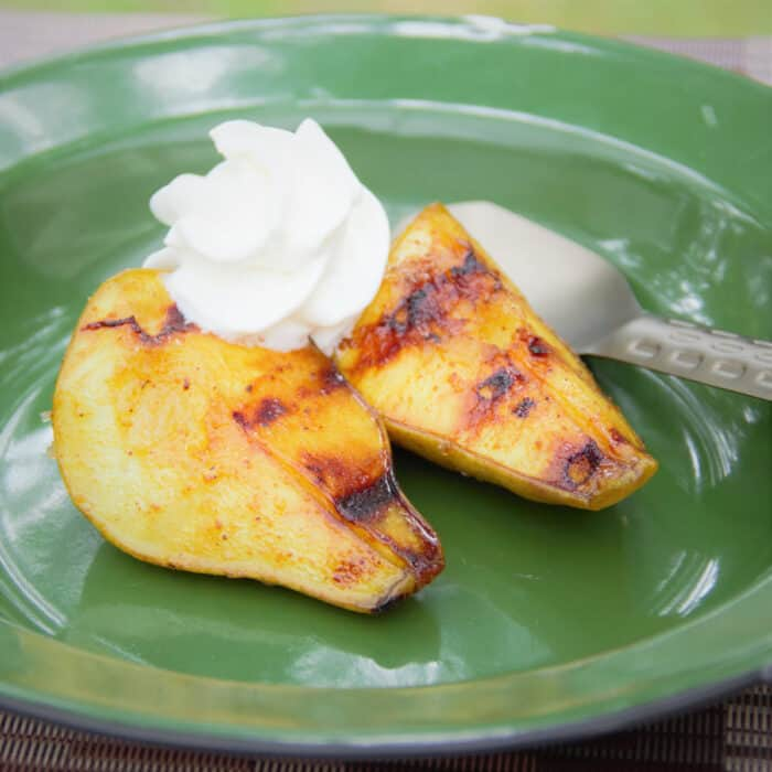 A green camp plate with two peieces oturmeric grilled pears and a side of whipped cream.